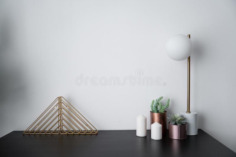 Composition of gold bookshelf and copper vase and gold stylish table lamp in mid century modern design standing on black wooden to royalty free stock photo