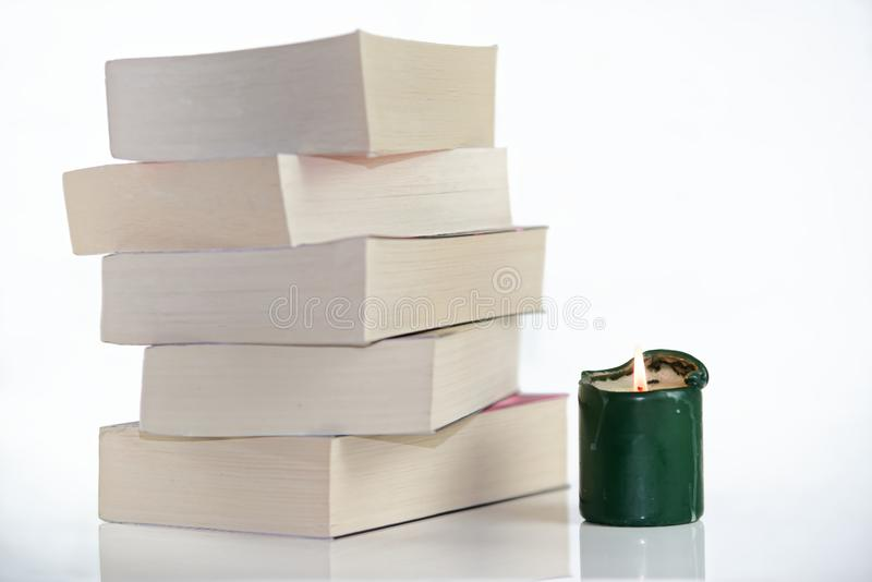 Green burning candle and pile of books against white background. Composition of green burning candle and pile of books against white background royalty free stock photo