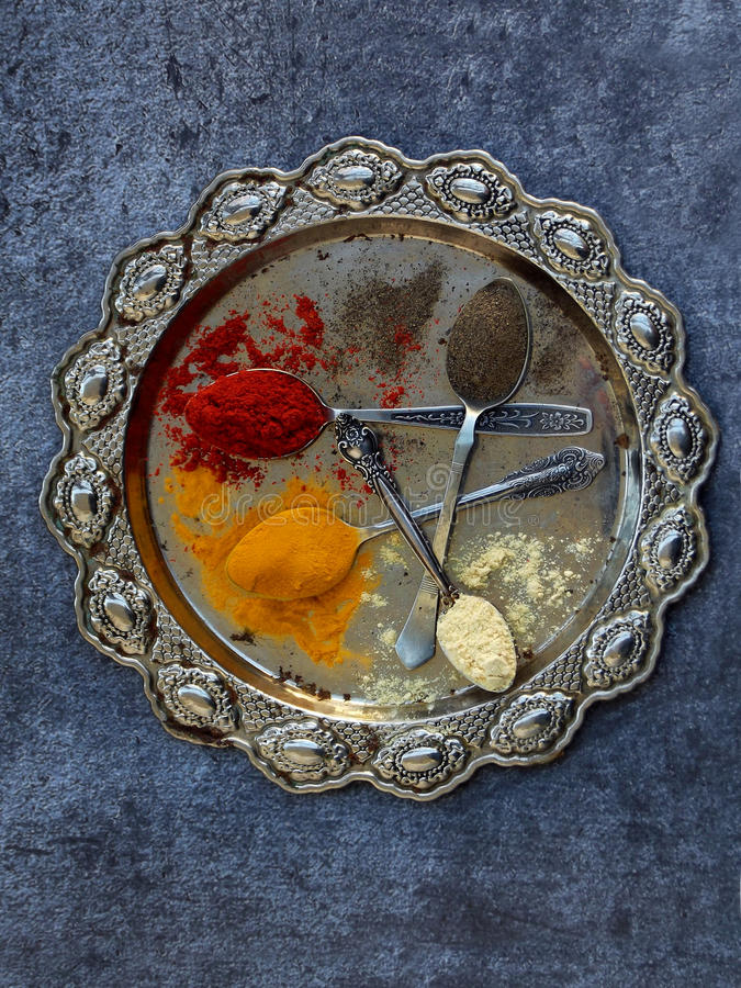 The composition of ground spices in a spoon on a metal dish. Paprika, turmeric, ginger, black pepper. Top view.  stock image