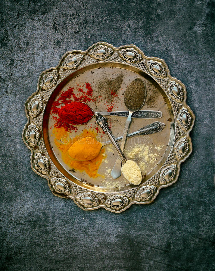 The composition of ground spices in a spoon on a metal dish. Paprika, turmeric, ginger, black pepper. Top view.  royalty free stock photo