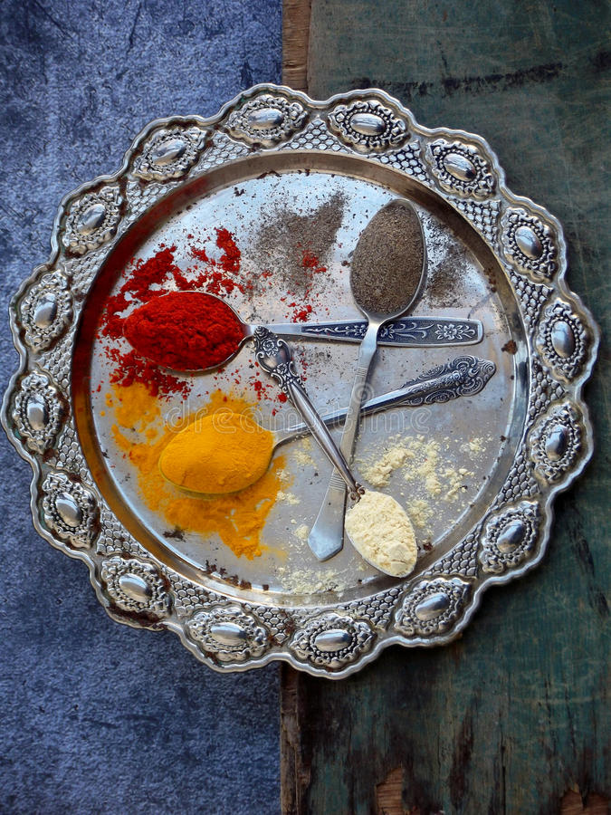 The composition of ground spices in a spoon on a metal dish. Paprika, turmeric, ginger, black pepper. Top view.  stock photography