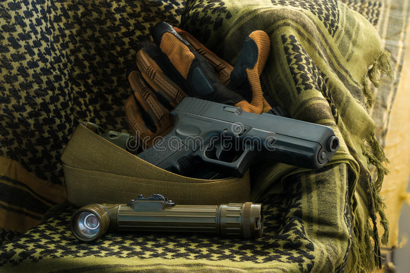 Composition of gun, angle-head flashlight and tactical gloves lying on shemagh royalty free stock photo