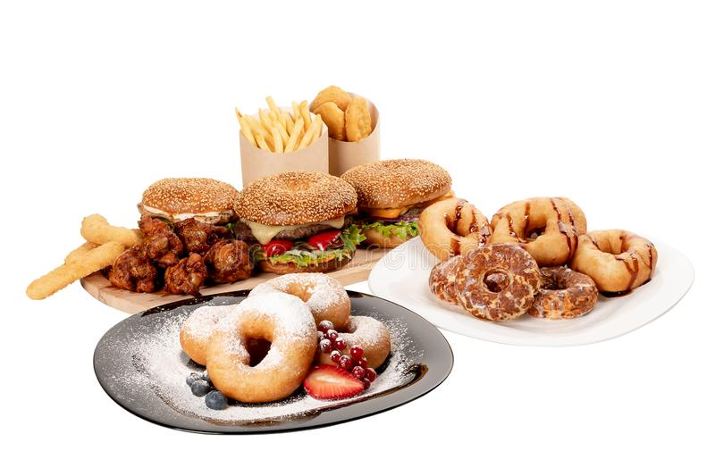 Composition of hamburgers, fries, donuts, nuggets, cheese sticks and chicken legs on white isolated background royalty free stock photography