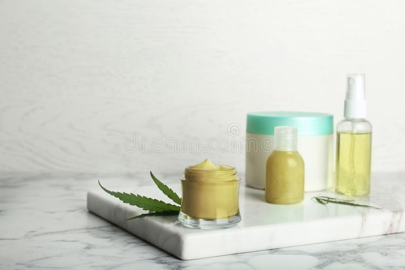 Composition with hemp lotion on marble table stock photography