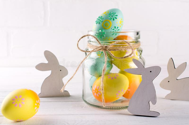 Composition with homemade Easter decor. Glass jar with colorful Easter eggs and wooden rabbits. On white background stock photo
