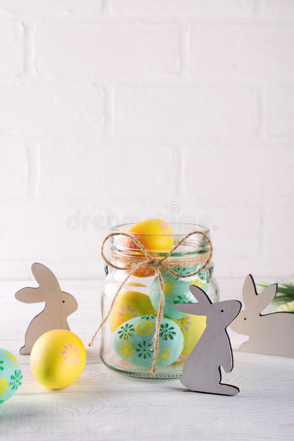 Composition with homemade Easter decor. Glass jar with colorful Easter eggs and wooden rabbits. On white background royalty free stock photos