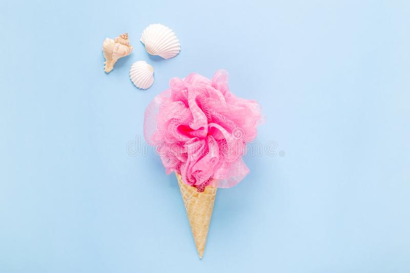 Composition of ice cream cone with pink wisp of bast on a light blue background. Bathroom cosmetic accessories. Flat Lay. Top View royalty free stock photo