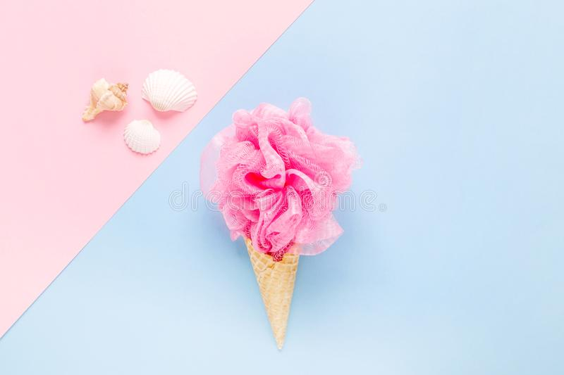 Composition of ice cream cone with pink wisp of bast on a light blue background. Bathroom cosmetic accessories. Flat Lay. Top View stock image