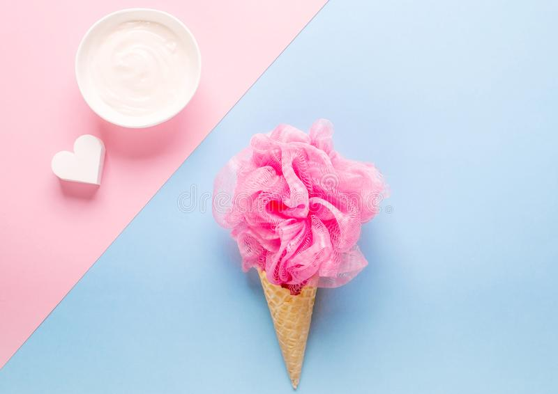 Composition of ice cream cone with pink wisp of bast on a light blue background. Bathroom cosmetic accessories. Flat Lay. Top View royalty free stock images