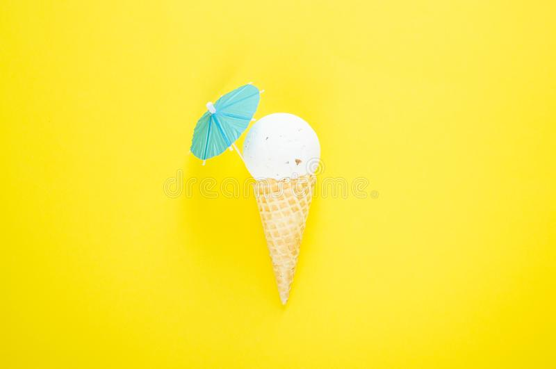 Composition of ice cream cone with white bath ball and beach umbrella. Bathroom cosmetic accessories. Flat Lay. Top View. Summer creative concept stock image