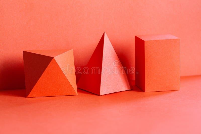 Composition immobile vivante en vie de tendance de chiffres géométriques de corail de couleur Belle pyramide tridimensionnelle re photographie stock