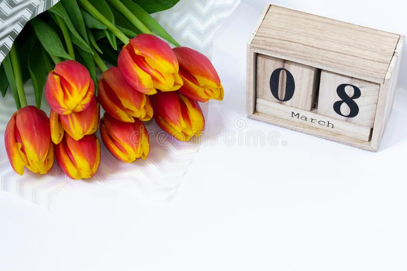Composition for International Women`s Day of bouquet of red tulip button flowers and wooden cubic calendar with date of 8 March. Beauty blog style, workplace stock photography