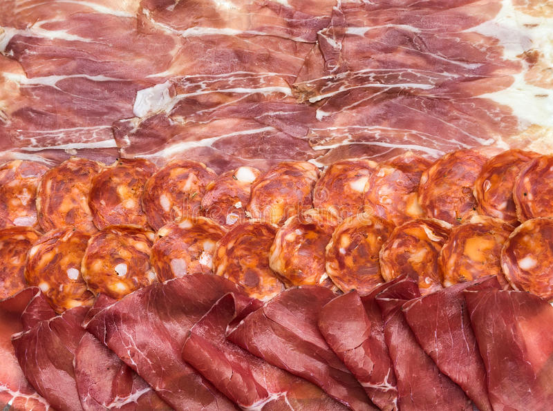Composition of italian cured meat types. Salami, bresaola and Prosciutto di Parma slices, top view royalty free stock images