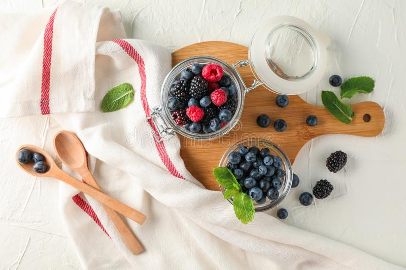 Composition with kitchen accessories and berries. On white cement background stock images