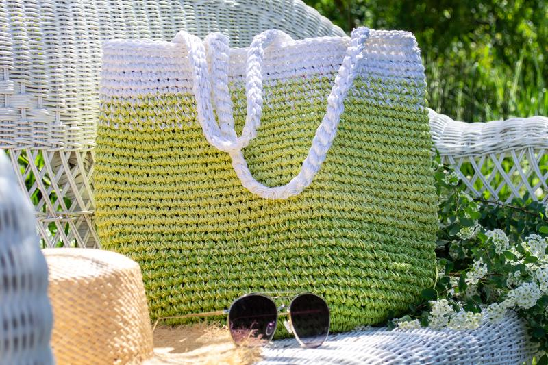 Composition of knitted hand-made green-white bag, straw hat and sun glasses on white  wicker chair with blooming spirea bouqet royalty free stock image