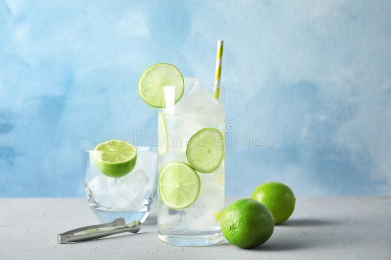 Composition with lime drink and ice cubes in glass on table stock photography