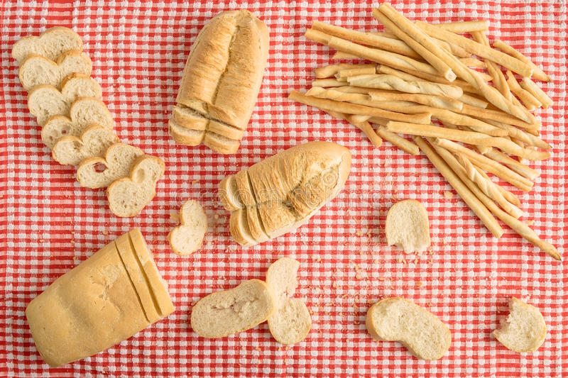 Composition of loaves and breadsticks over red and white checker table cloth with bread slices view from above stock photos