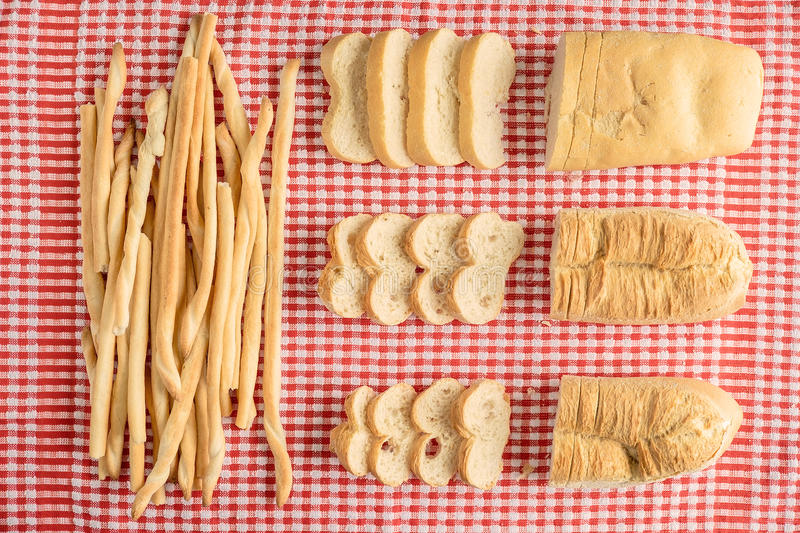 Composition of loaves and breatsticks over red and white checker table cloth with bread slices view from above stock photography