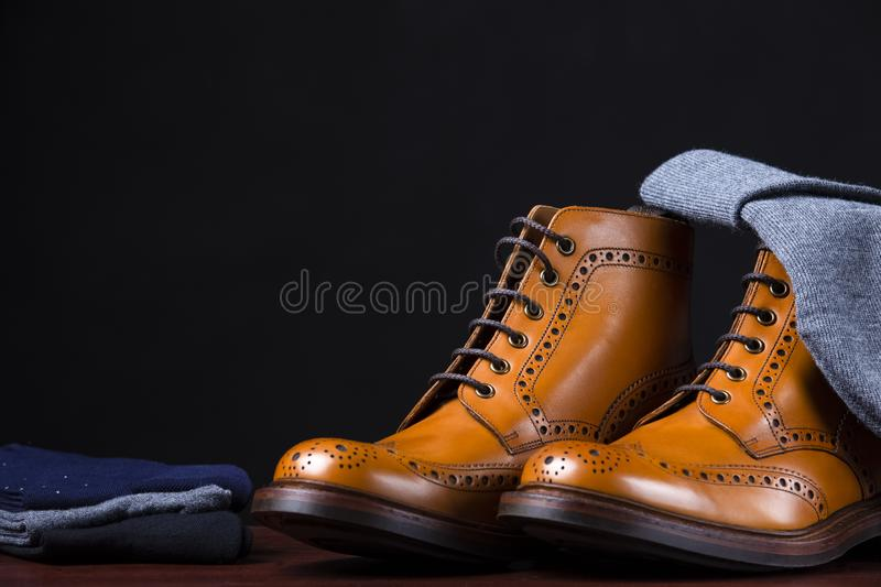 Composition Made Up of Mens Fashionable Tanned Brogues Boots, Warm Hat and Batch of Socks Laid Close. Isolated Over Black. Horizontal Shot royalty free stock photography