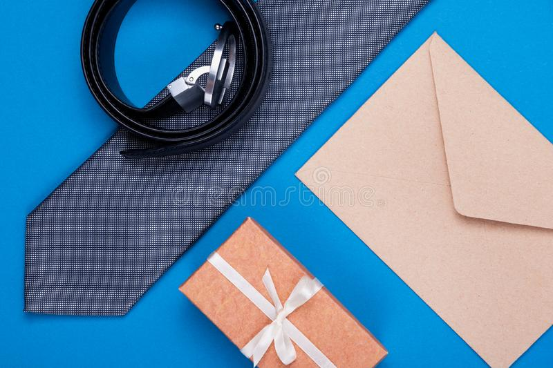 Composition of grey silver neck tie, gift box, craft envelope and belt on blue cyan background. Fashionable man`s concept. Composition of man`s accessories grey stock image