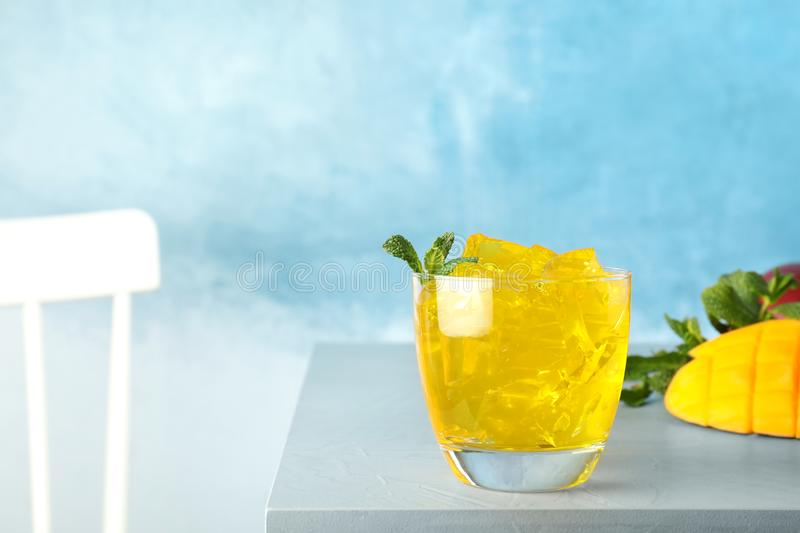 Composition with mango jelly in glass on table against color background stock photography