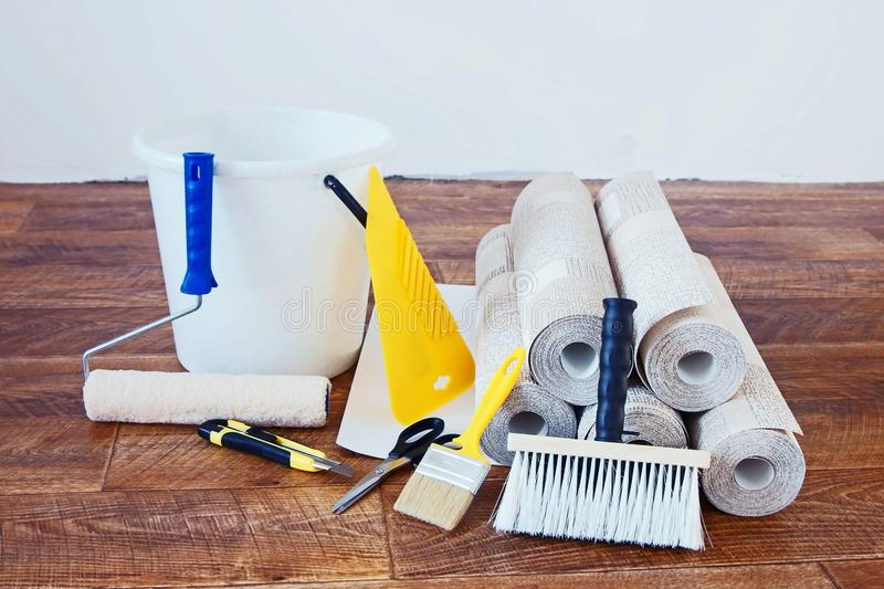 Composition with many rolls of wallpaper and various tools for home repair. Indoors royalty free stock images