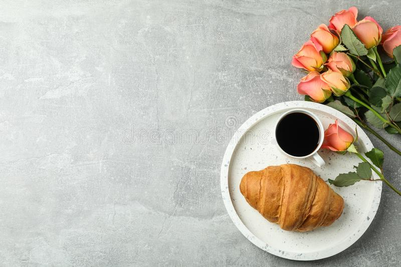 Composition with marble tray, cup of coffee, croissant, roses and space for text on grey background stock image