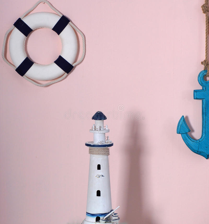 Composition in a marine style. The toy circle and the anchor hang on a wall of pink color, the lighthouse stands side by side, cas stock images