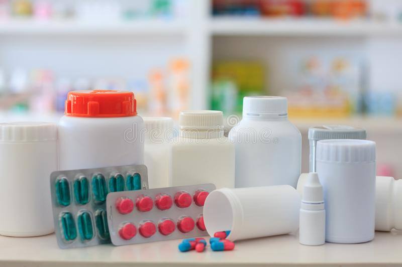 Composition of medicine bottles and pills with pharmacy store. Shelves background stock photos