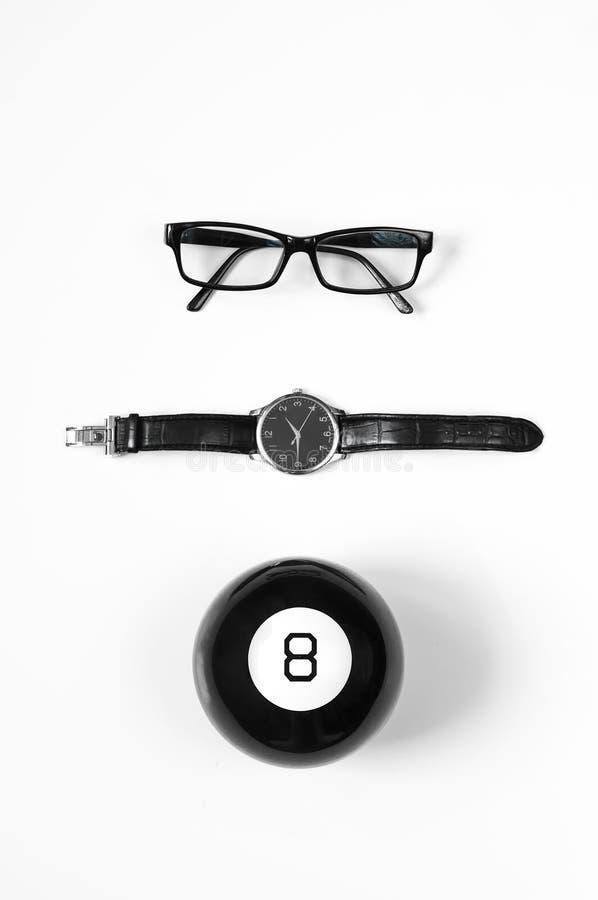 Composition minimalistic noire et blanche : verres, montres et boule magique 8 photographie stock libre de droits