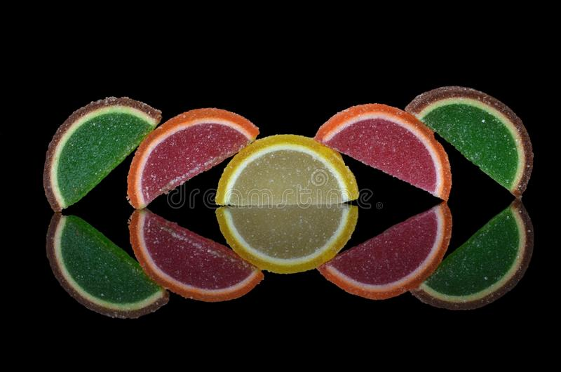 Composition of multi-colored citrus marmalade slices. On glass with symmetrical bright reflection royalty free stock photos