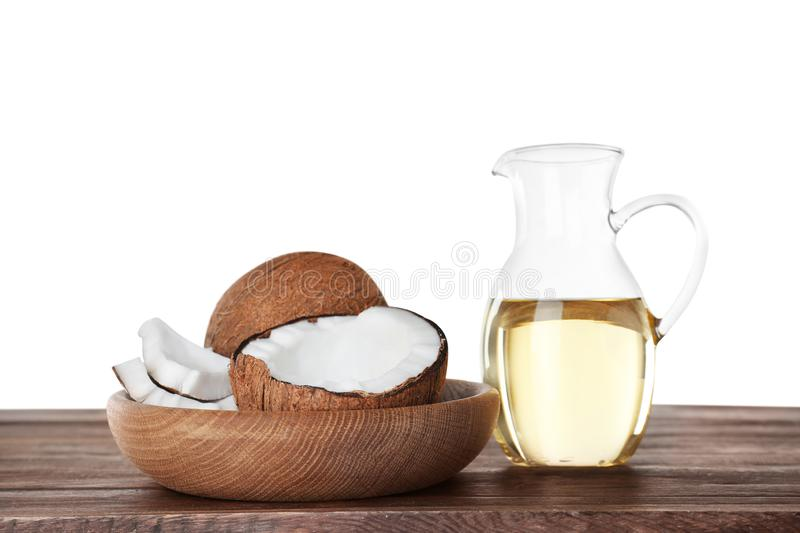 Composition with natural organic oil and ripe  on wooden table against white background royalty free stock photography