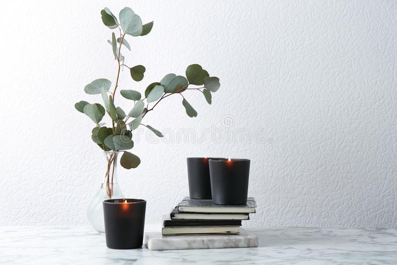 Composition with notebooks, burning candles and  branches on table. Composition with notebooks, burning candles and green branches on table stock image