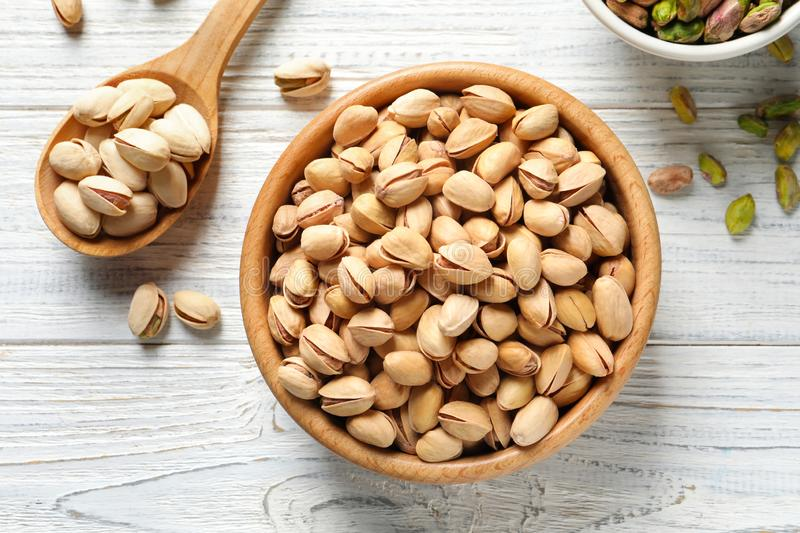 Composition with organic pistachio nuts in bowl on table, top view. Composition with organic pistachio nuts in bowl on wooden table, top view stock photos