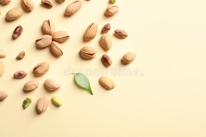 Composition with organic pistachio nuts on color background, flat lay. Space for text stock photo