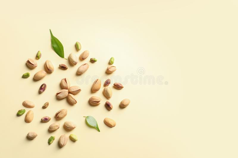 Composition with organic pistachio nuts on color background, flat lay. Space for text stock images