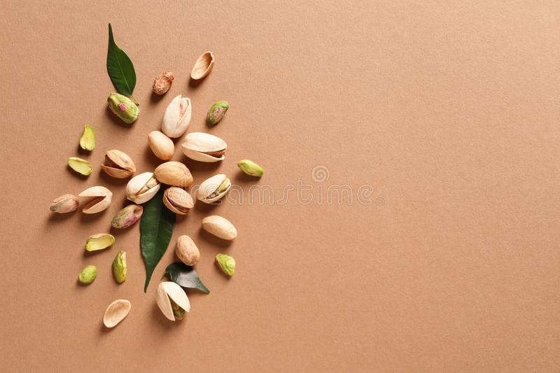 Composition with organic pistachio nuts on color background, flat lay. Space for text stock photos