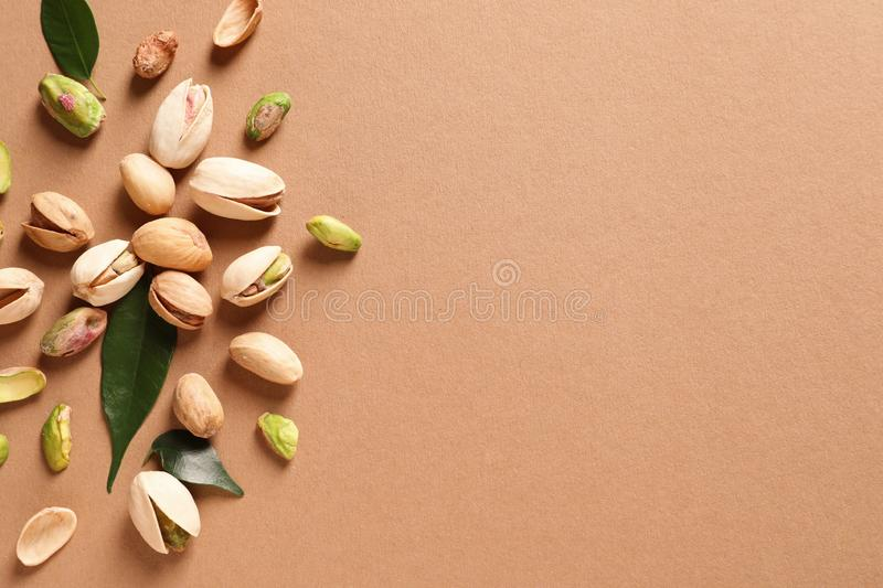 Composition with organic pistachio nuts on color background, flat lay royalty free stock photography