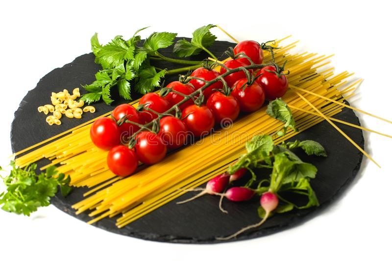 Composition of pasta fresh tomato, pepper, , radish on black stone board, white background. Composition of pasta fresh tomato, pepper, , radish on black stone stock photos