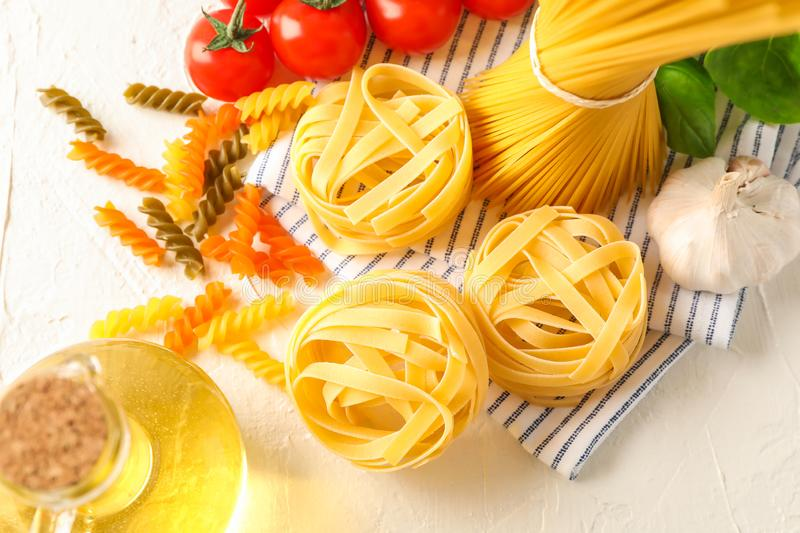 Composition with pasta, tomatoes, garlic, olive oil and kitchen towel on white background, space for text royalty free stock image