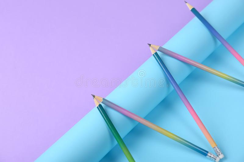 Composition with pencils and rolled paper. On color background. Space for text stock photo