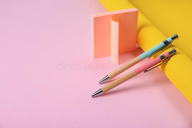 Composition with pens and sticky notes on color background. Space for text royalty free stock images