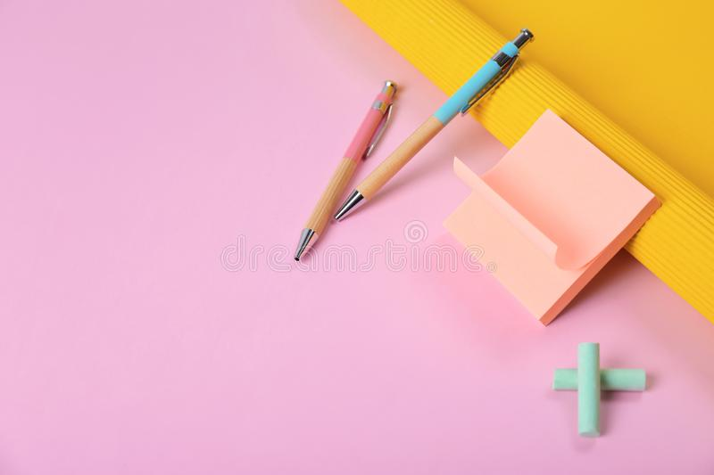 Composition with pens and sticky notes on color background. Space for text stock photography