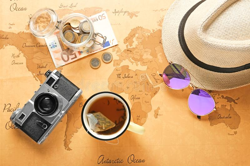 Composition with photo camera, hat, sunglasses, cup of tea and money on vintage world map. Travel planning concept stock photo