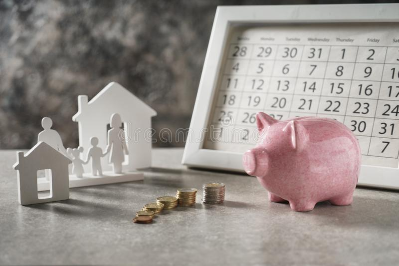 Composition with piggy bank, calendar and model of house and family on grey table. Concept of saving money for buying new house stock photography