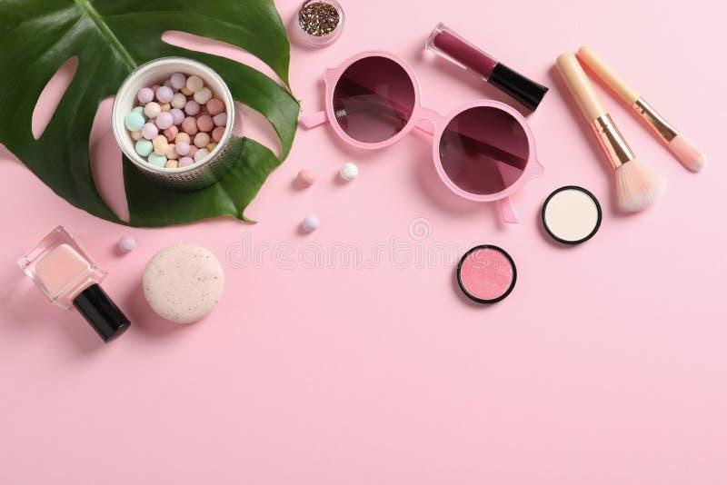 Composition plate en configuration avec des produits pour le maquillage décoratif sur le rose en pastel image libre de droits
