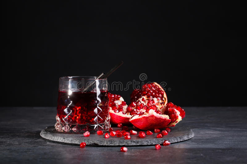 A composition of a pomegranate drink and cut garnet on a black background. Refreshing red cocktails. royalty free stock photo
