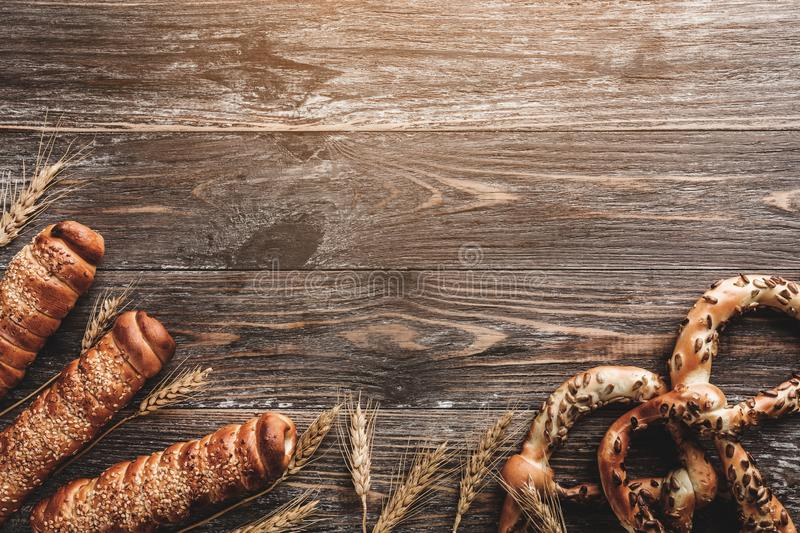 Composition of pretzels with sunflower seeds, spice of wheat and sausages in dough on wooden table. Copy space, light effect royalty free stock photo