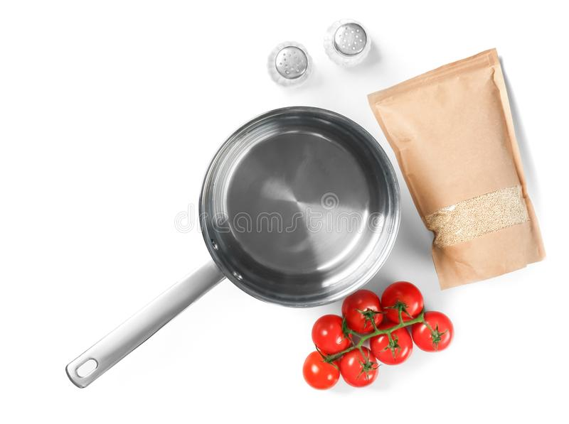Composition with raw quinoa, kitchen supplies and fr. Esh cherry tomatoes on white background stock photo