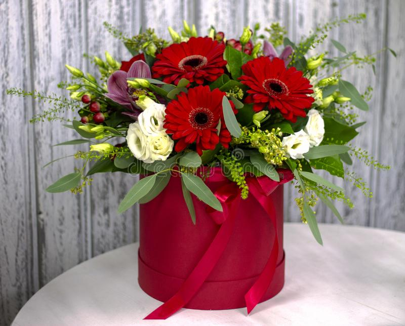 Bright composition with red gerberas in a hat box stock images